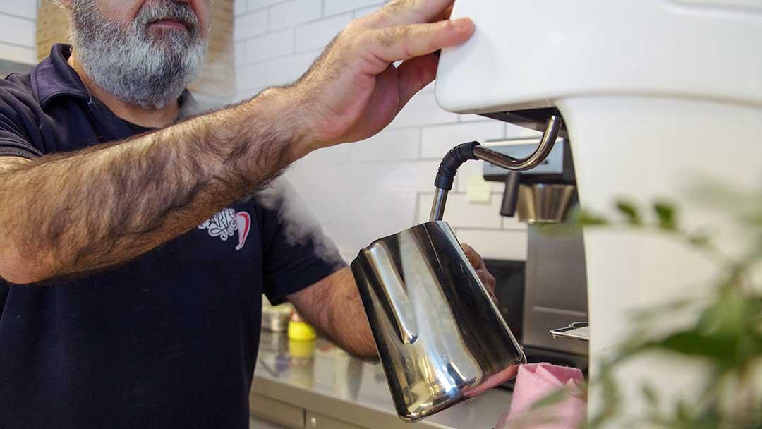 mann som lager kaffe bak disken